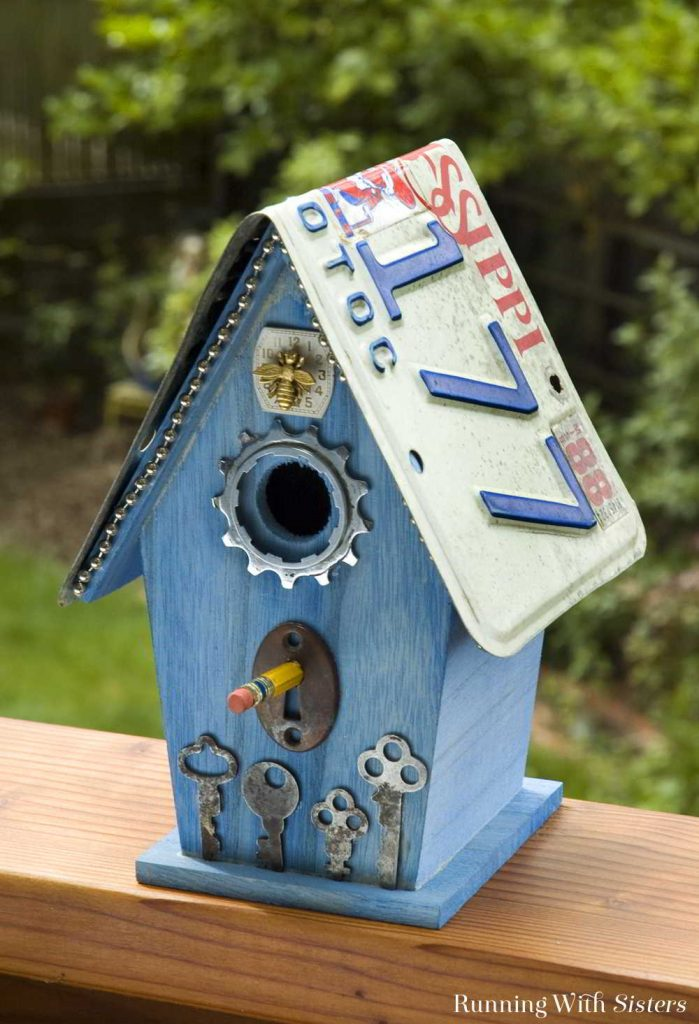 Turn a plain birdhouse into a Flea Bitten Embellished Birdhouse with skeleton keys, a bicycle gear, a rusty keyhole, and more!