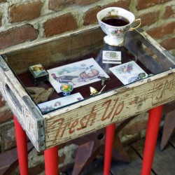Upcycle a flea market crate into a shadowbox crate table. Prop the glass top on wood pegs and add legs with screw-on plates.