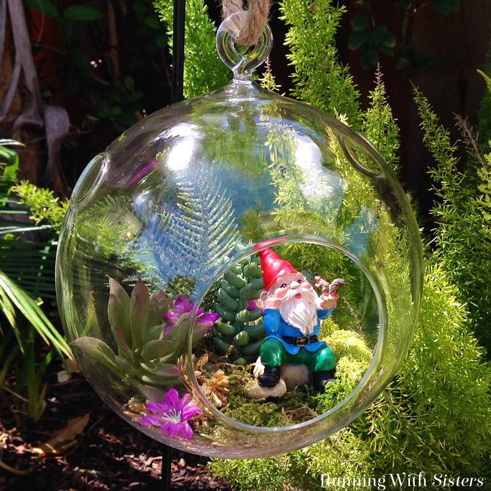 Create a succulent bubble garden with faux succulents and little garden gnome. The glass orb makes this bubble terrarium extra cute!
