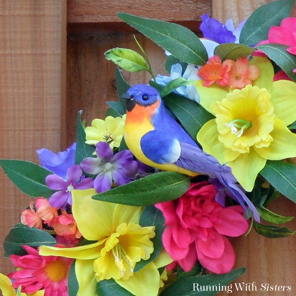 Make a colorful Summer Birdhouse Wreath featuring silk flowers of the season and a bright birdhouse! Add pretty craft birds to finish it off!