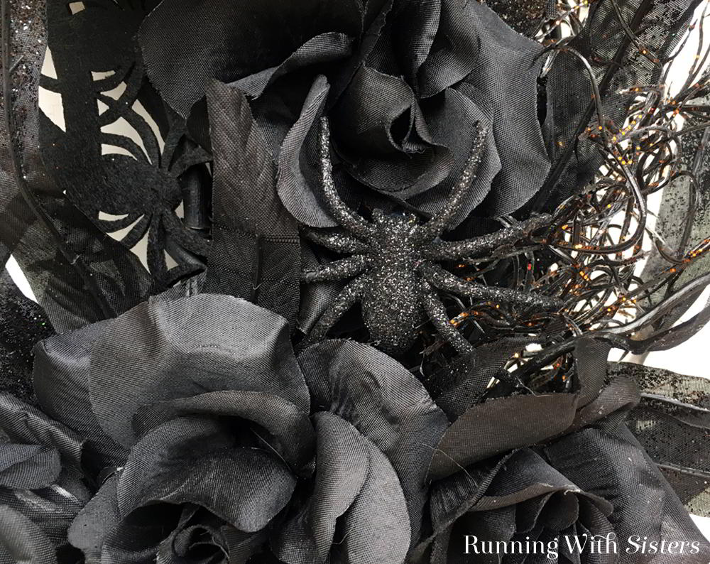 Make a spooky, sparkly Halloween Spider Wreath with a die-cut web placemat and lots of glittered black roses. A big orange bow ties it all up!