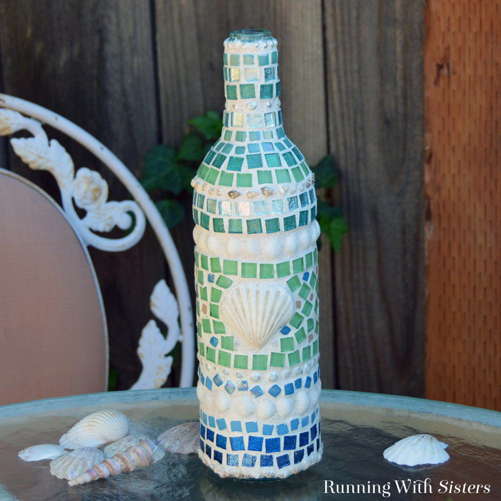 Create a mosaic wine bottle with shells and sea glass tiles. We'll show you how to make the mosaic and grout it too with our video tutorial!