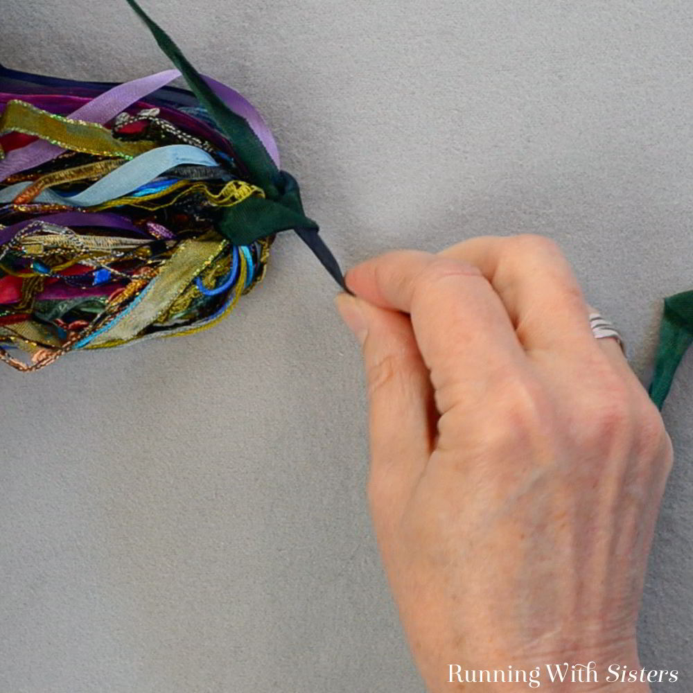 Make a tassel from scraps of ribbon and trims. It's easy! We'll show you how to tie the trims into a decorator tassel to wear or use as a keychain!