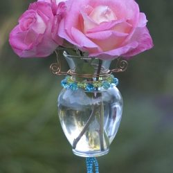 Turn a dollar store vase into a beaded hanging bud vase. It's easy! We'll show you how to use copper wire and beads to make this pretty hanging bud vase!