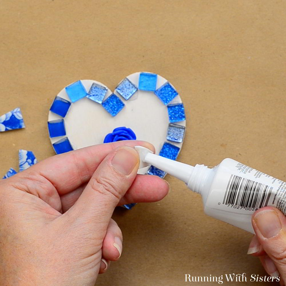 Make a Broken China Heart Mosaic! In this step by step DIY mosaic tutorial, you'll learn how to glue down the tiles, how to mix the grout, and how to grout the tiles.