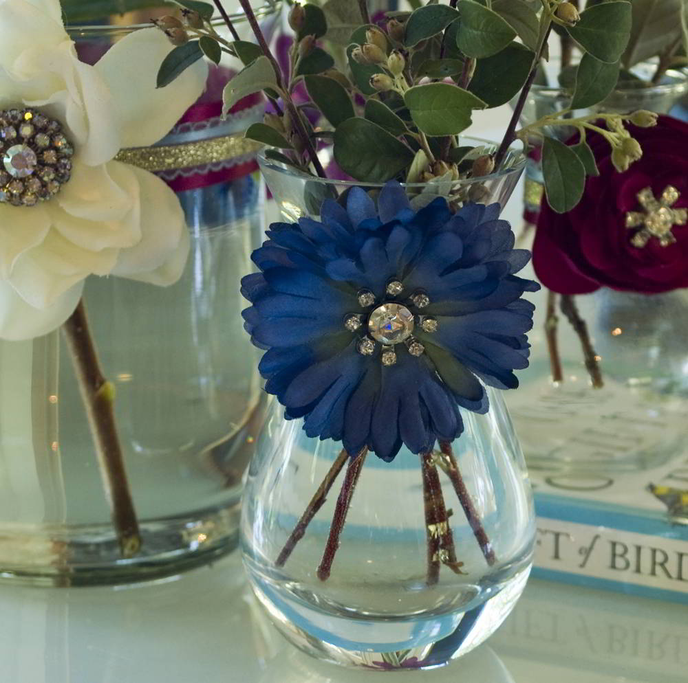 Dress up dollar store vases with playful flowers and brooches. This is an easy and cheap decorating idea!