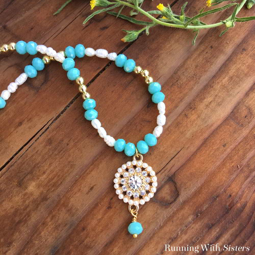 Make a gorgeous Pearl And Aqua Crystal Beaded Necklace featuring a pearl and rhinestone circle pendant. We made a complete video tutorial to show you how!